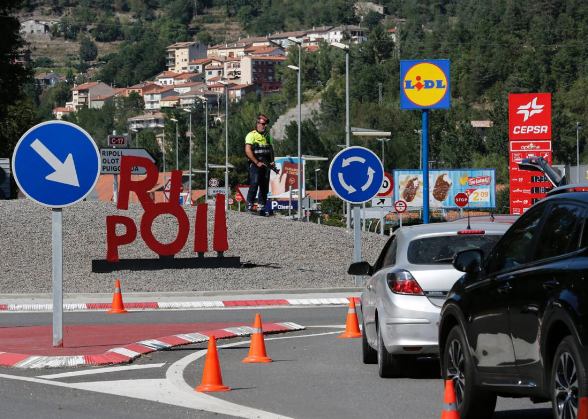 A Police officer stands guard at a road control in Ripoll on August 20, 2017, as part of an operation to find a suspect of Barcelona's attack.