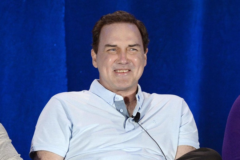 Norm Macdonald in a chair onstage for a panel discussion.