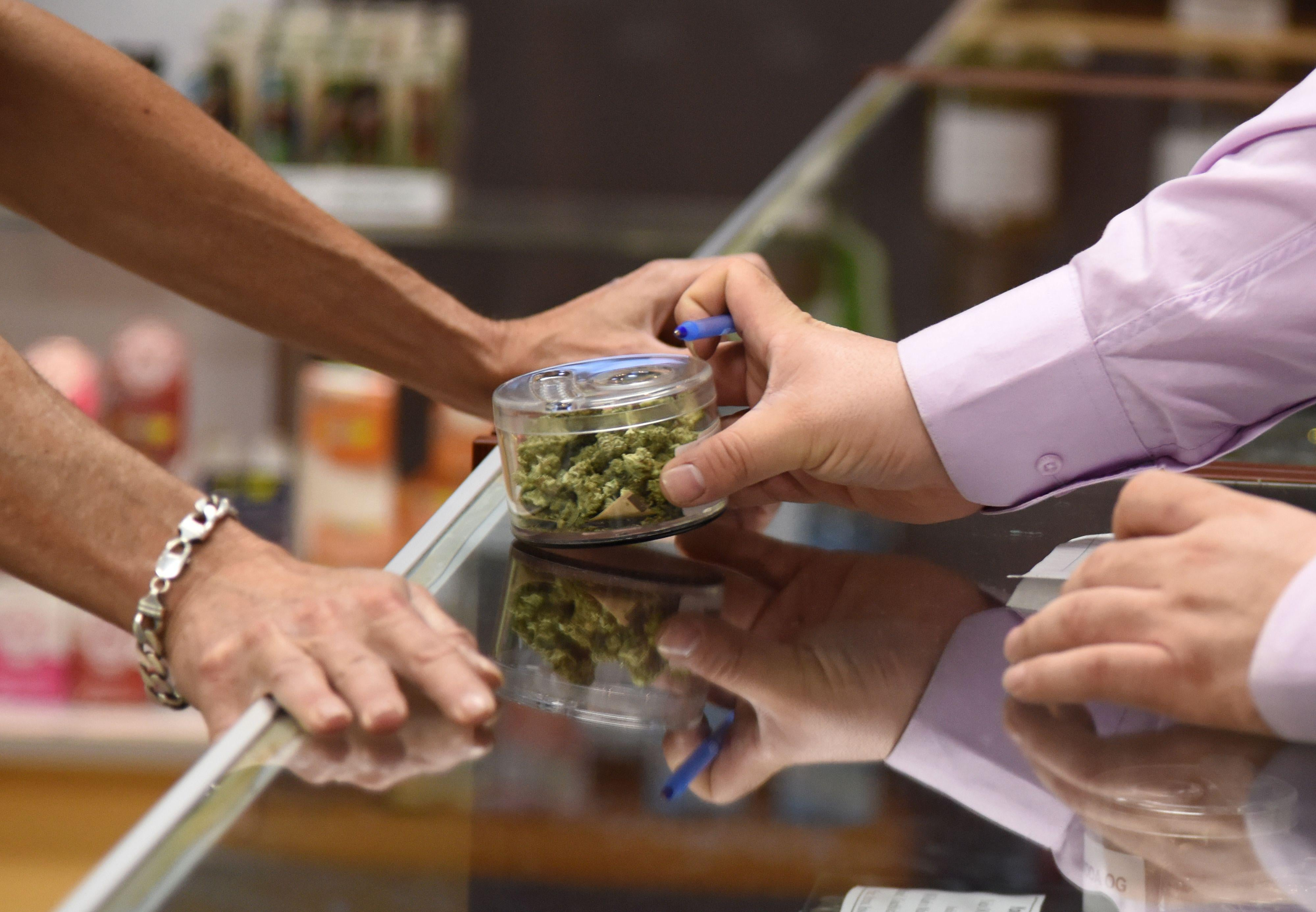 A budtender (right) shows cannabis buds to a customer at the Green Pearl Organics dispensary on the first day of legal recreational marijuana sales in California, January 1, 2018 at the Green Pearl Organics marijuana dispensary in Desert Hot Springs, California.