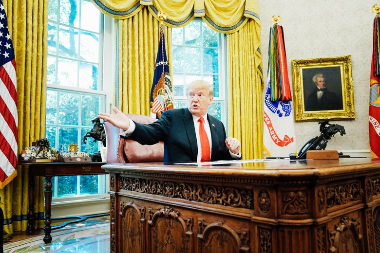 Donald Trump gestures while sitting at his desk in the Oval Office.