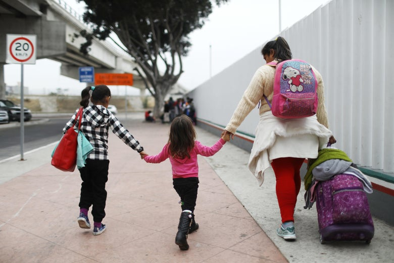 A migrant mother walks with her two daughters and their baggage along a border fence on their way to the port of entry to ask for asylum in the U.S.