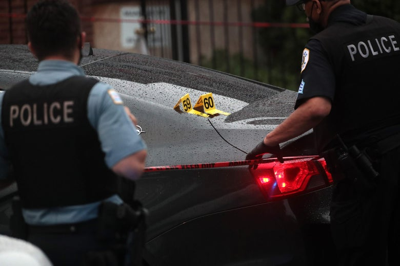 Shell casings labeled 59 and 60 rest on a bullet-riddled car as police investigate the scene of a shooting in the Auburn Gresham neighborhood of Chicago on July 21, 2020