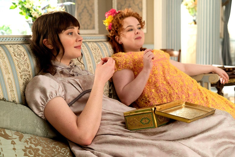 Claudia Jessie and Nicola Coughlan sit slumped on a couch. Jessie wears a high-neck, satiny gown in a muted beige tone; Coughlan wears a busy yellow and orange gown with ruffles.