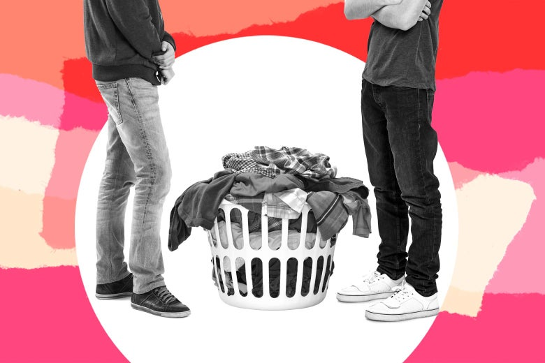 Two young men stand beside a hamper.