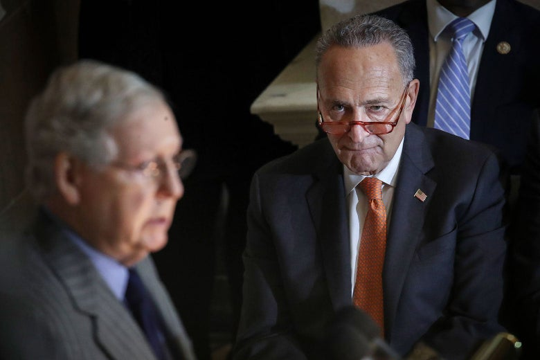 Schumer looks over his glasses at McConnell as he stands behind a podium.