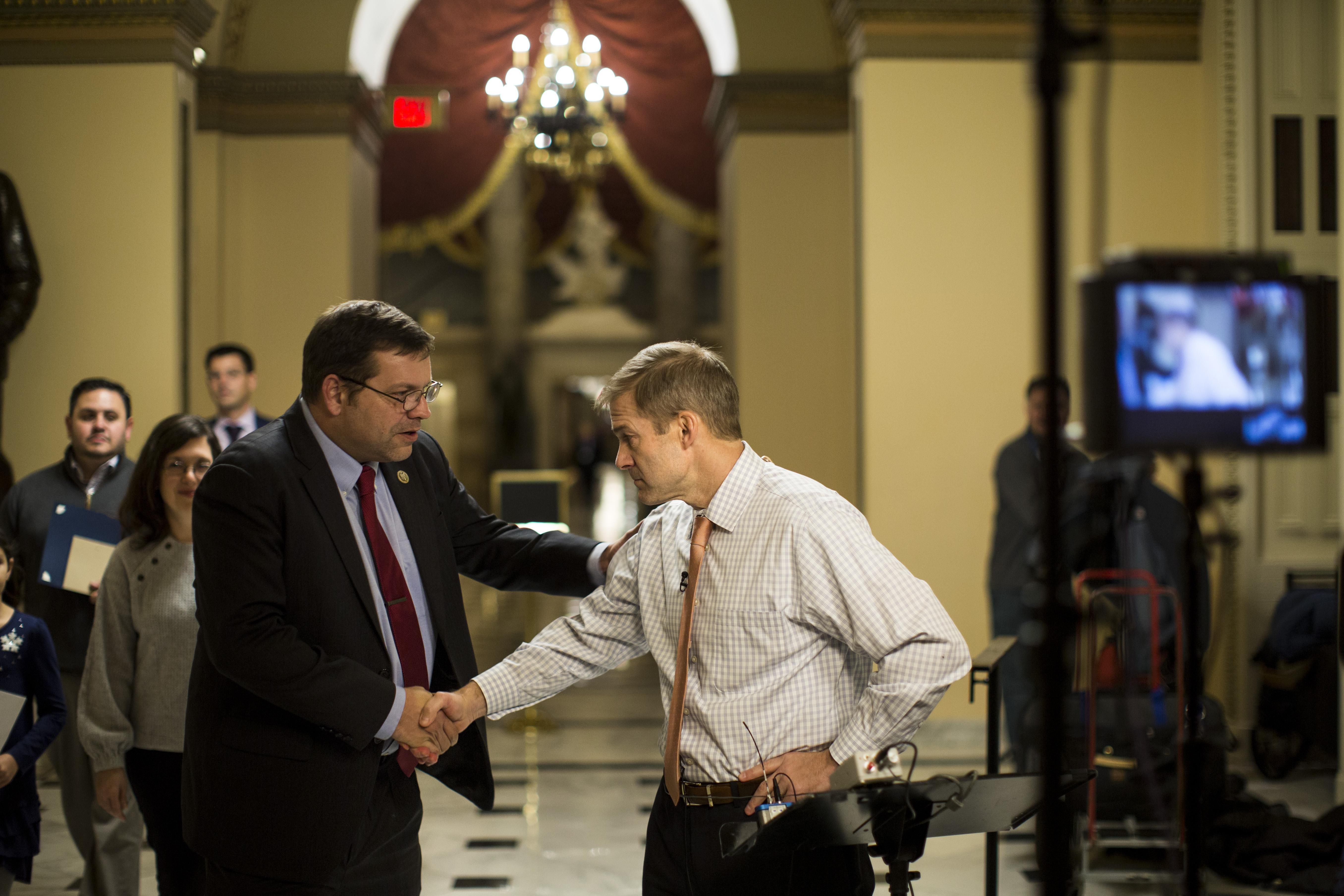 Tom Garrett grabs the shoulder of and shakes hands with Jim Jordan.