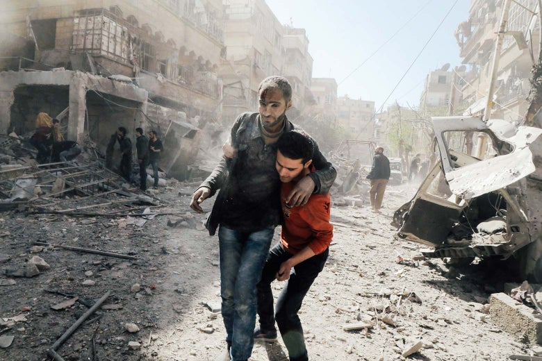 A Syrian man helps evacuate an injured victim following Syrian government air strikes on the Eastern Ghouta rebel-held enclave of Douma, on the outskirts of the capital Damascus on March 20, 2018.
