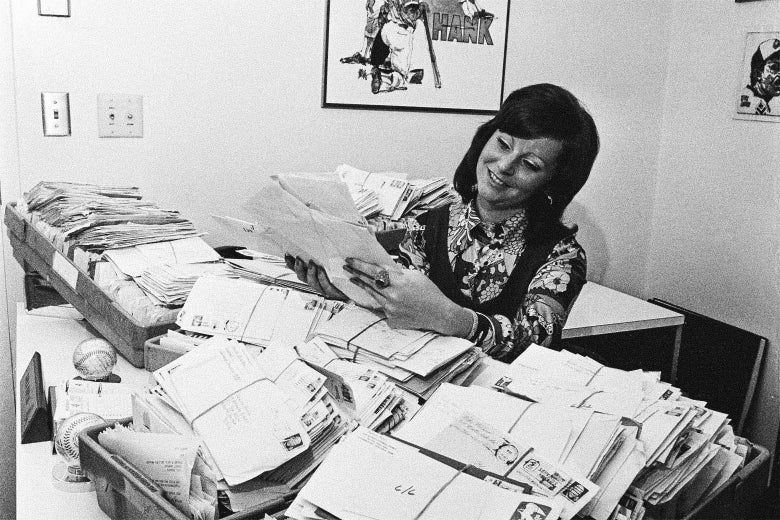 A woman sitting at a desk that's covered with huge piles of unopened letters.