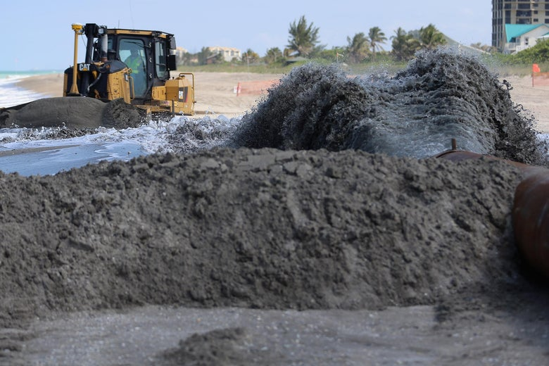 FORT PIERCE, FL - MAY 17:  A bulldozer is used to push sand from a discharge pipe into place during a federally funded shore protection project by Great Lakes Dredge and Dock on May 17, 2013 in Fort Pierce, Florida. As cities along the East Coast prepare for the start of the hurricane season, officials say the area encompasing Fort Pierce beach has been in dire need of repair since Hurricane Sandy last year made worse an area already suffering significantly from erosion. Some experts say shore restoration projects can help reduce the physical and economic damage from waves, storm surge, and the resulting coastal flooding in a hurricane.  (Photo by Joe Raedle/Getty Images)