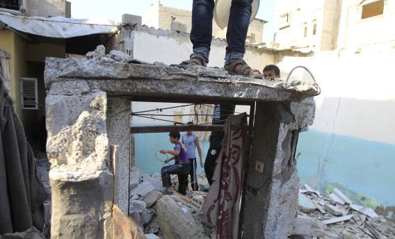 Palestinian boys amid the rubble of a damaged house targeted by an overnight Israeli air strike in the southern Gaza Strip.