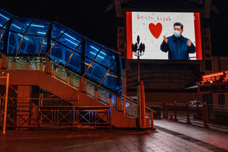 Outside a nearly empty railway station, a large monitor shows an image of Chinese President Xi Jinping wearing a mask next to a heart.