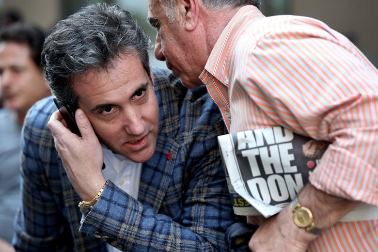 Michael Cohen leans over while holding a cell phone to his right ear while an unidentified man holding a New York Post headline about Donald Trump speaks into his other ear.