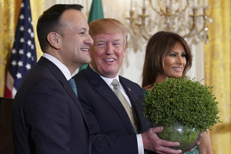 President Donald Trump picks up a bowl of shamrocks as Ireland's Prime Minister Leo Varadkar and First Lady Melania Trump look on in the East Room of the White House March 15, 2018 in Washington, D.C.