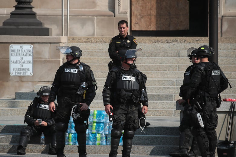 Six police officers dressed in riot gear stand in front of a courthouse.