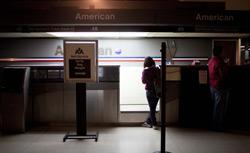 Travelers stand at an empty American Airlines ticket counter. Click image to expand.