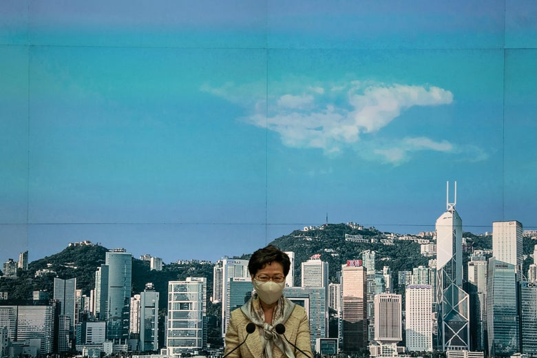 Carrie Lam is seen wearing a face mask. A city skyline is seen in the background.