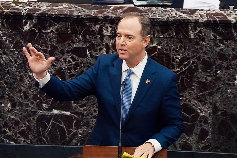 Adam Schiff raises his hand while speaking at a lectern
