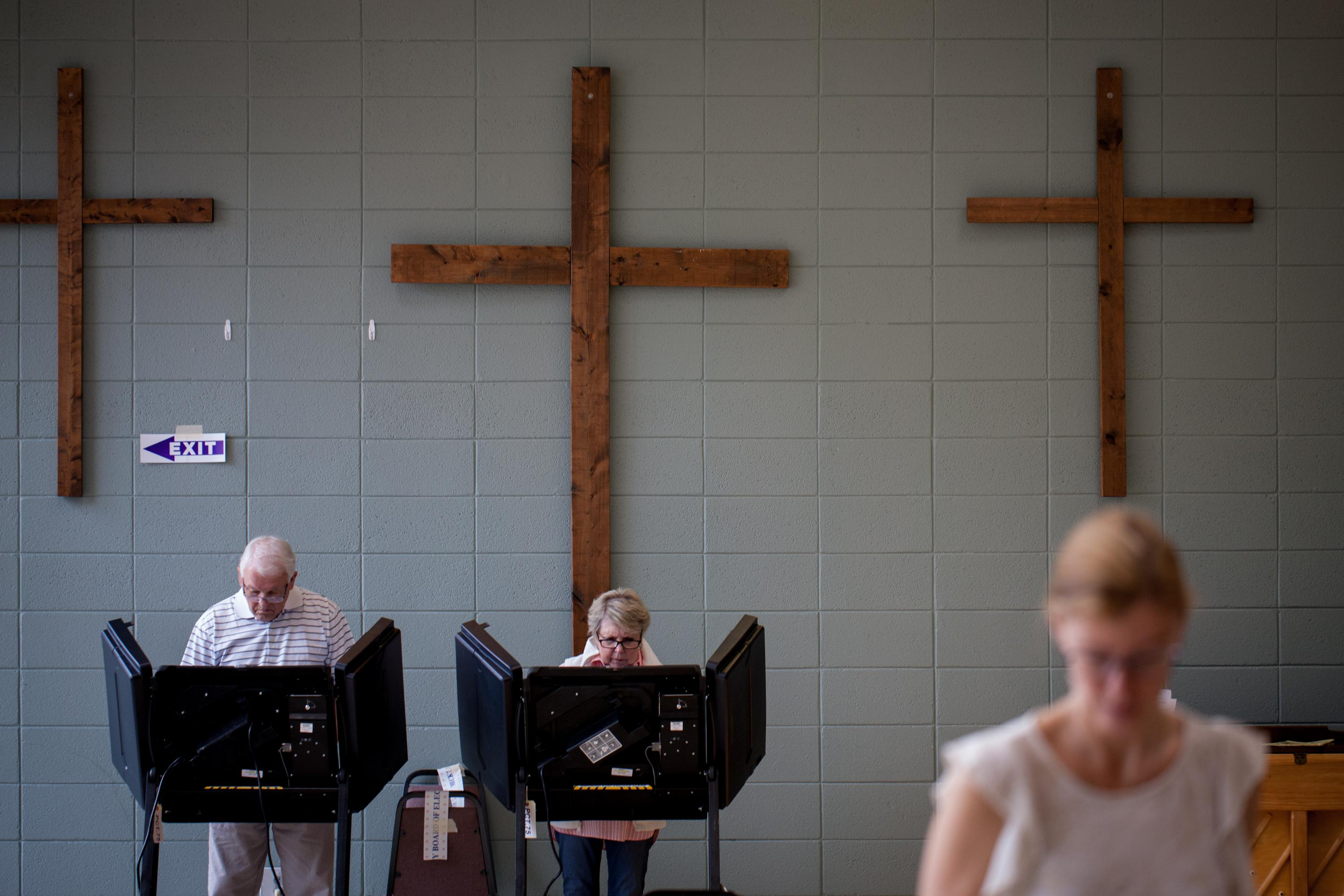Two people at voting booths. Three Christian crosses hang on the wall behind them.