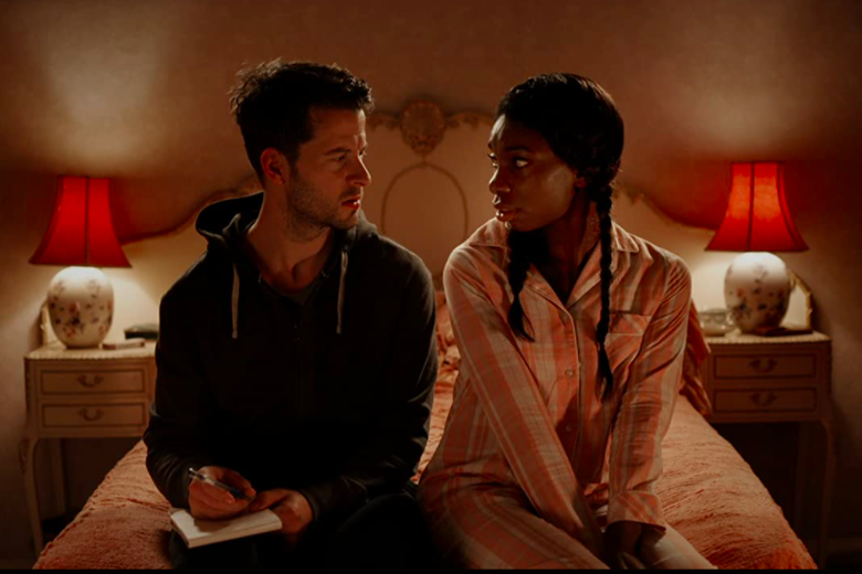 Robert Lonsdale, holding a notepad and pen, sits on the edge of a bed with Michaela Coel.