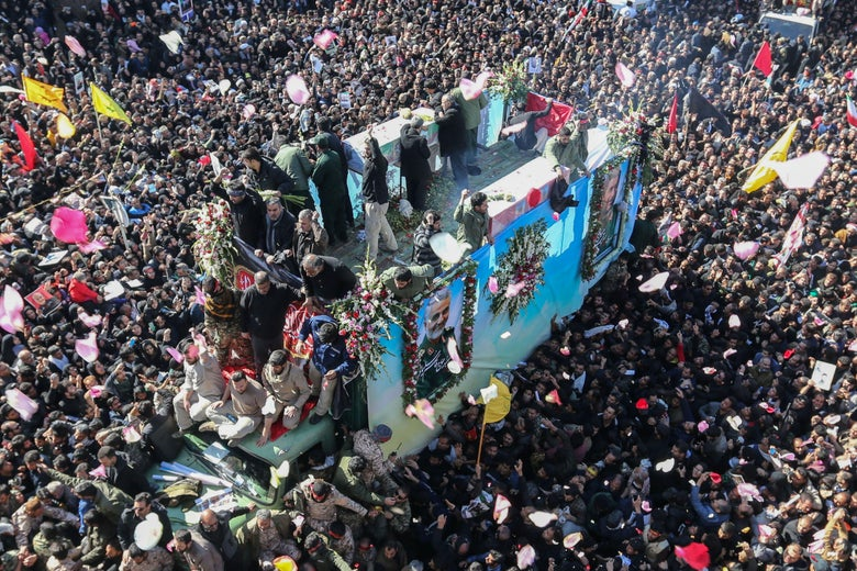 A large crowd surrounds a truck with people on top of it. The truck features a photo of Qassem Soleimani framed in flowers on the side.