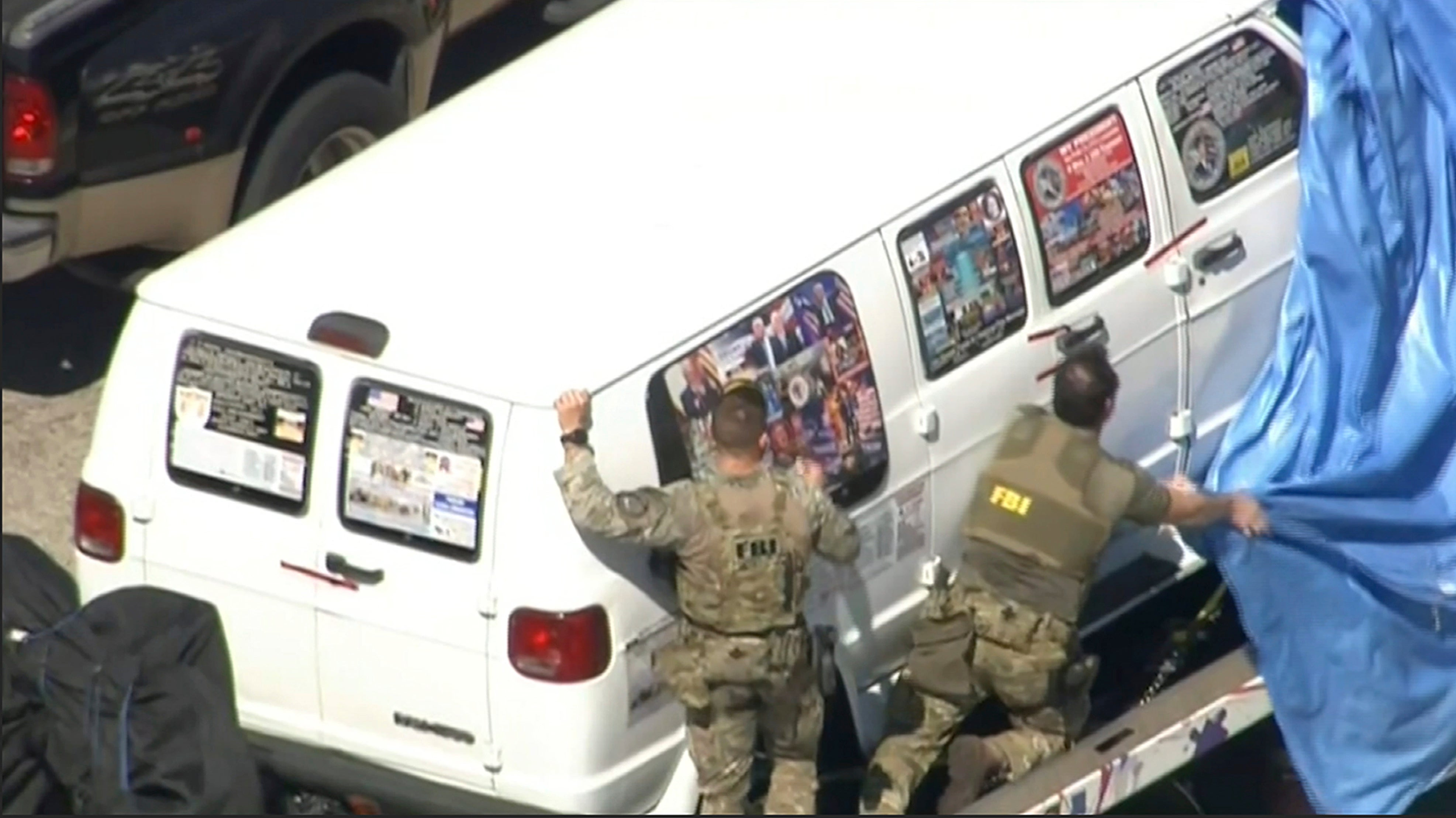 FBI agents covering a van after the tarp fell off.