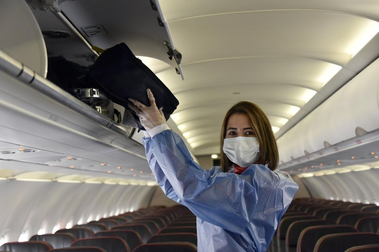 A woman wearing protective equipment, including a mask, stands in the aisle of an empty plane as she puts a bag into an overhead compartment.