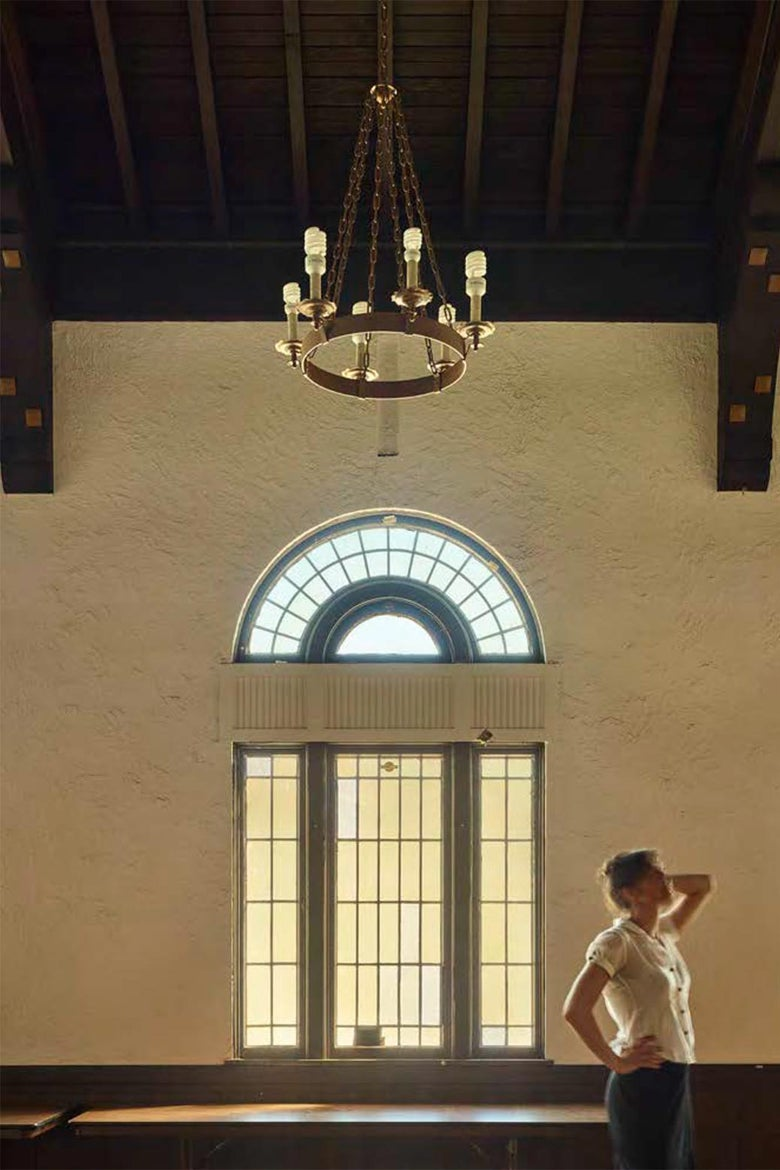 A woman holds her hand to her head and looks up at the room while standing beside a large window and below a chandelier.