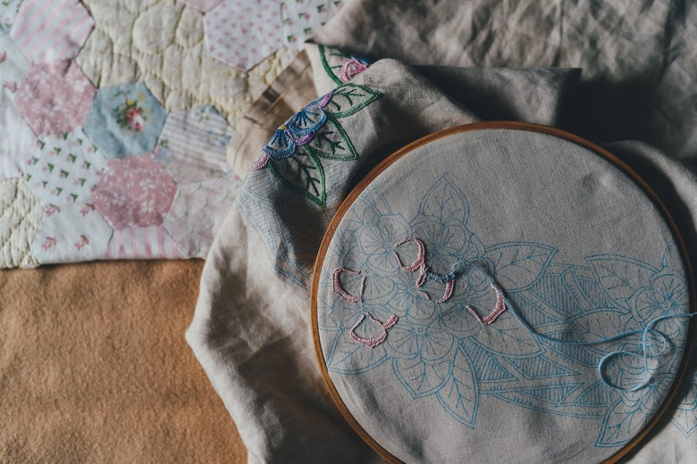 The beginning of an embroidered design lies inside a wooden hoop. A quilt lies in the background.