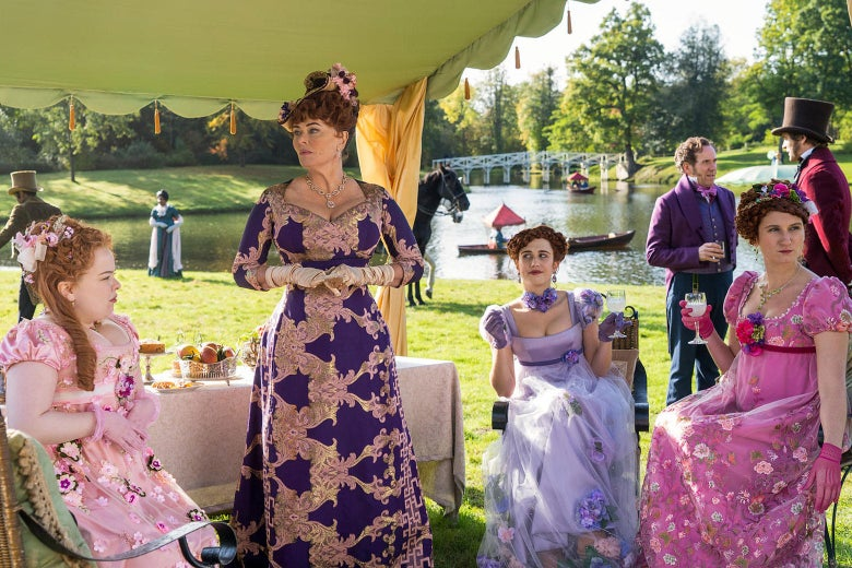 A garden party scene. From left to right: Nicola Coughlan as Penelope Featherington wears a light pink gown with flowers; Polly Walker as Lady Portia Featherington wears a deep purple gown with a bold repeating pattern; Harriet Cains as Philippa Featherington wears a satiny lavender gown with a floral choker and a sheath layered skirt; Bessie Carter as Prudence Featherington wears a bright pink gown with flowers.