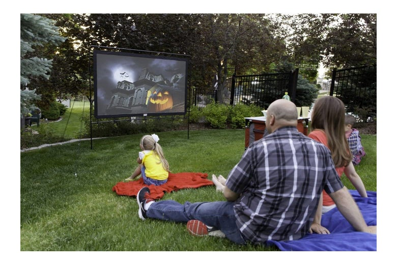 Family sitting on grass watching something on an outdoor screen