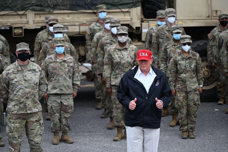 Donald Trump, in a blue jacket and red USA cap, stands in front of rows of National Guardsmen wearing camouflage, sunglasses, and masks. Trump is giving two thumbs up.