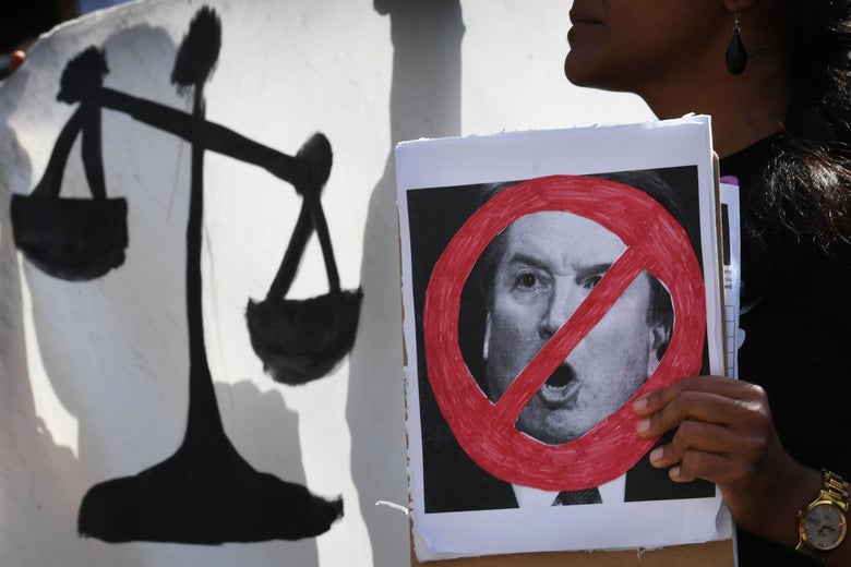 A woman holding a poster showing Kavanaugh's face crossed out, in front of a poster showing the scales of justice.