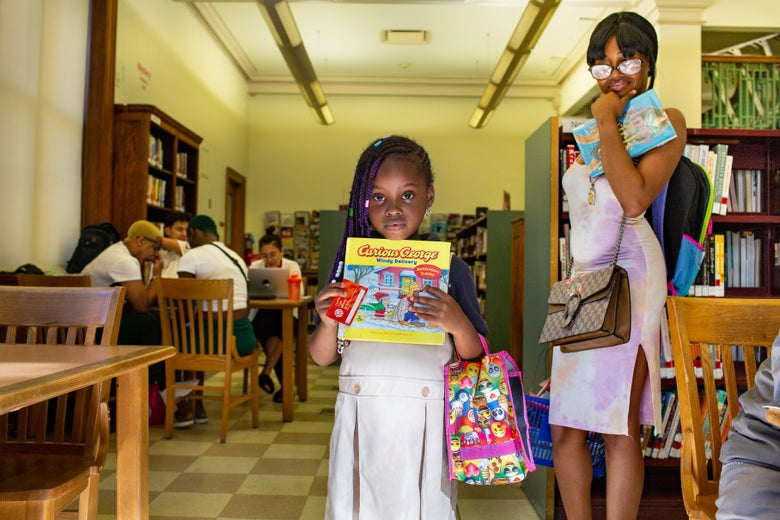 A girl holds a Curious George book and her library card proudly as a young woman looks on. A group of teens hang out at a table in the background.