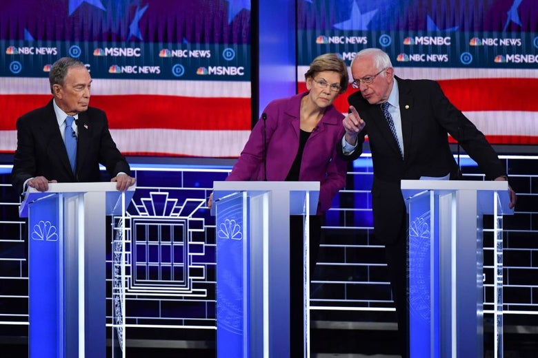 Bloomberg, standing at his lectern, looks to his left with pursed lips while Warren and Sanders lean toward each other as Sanders speaks to Warren.