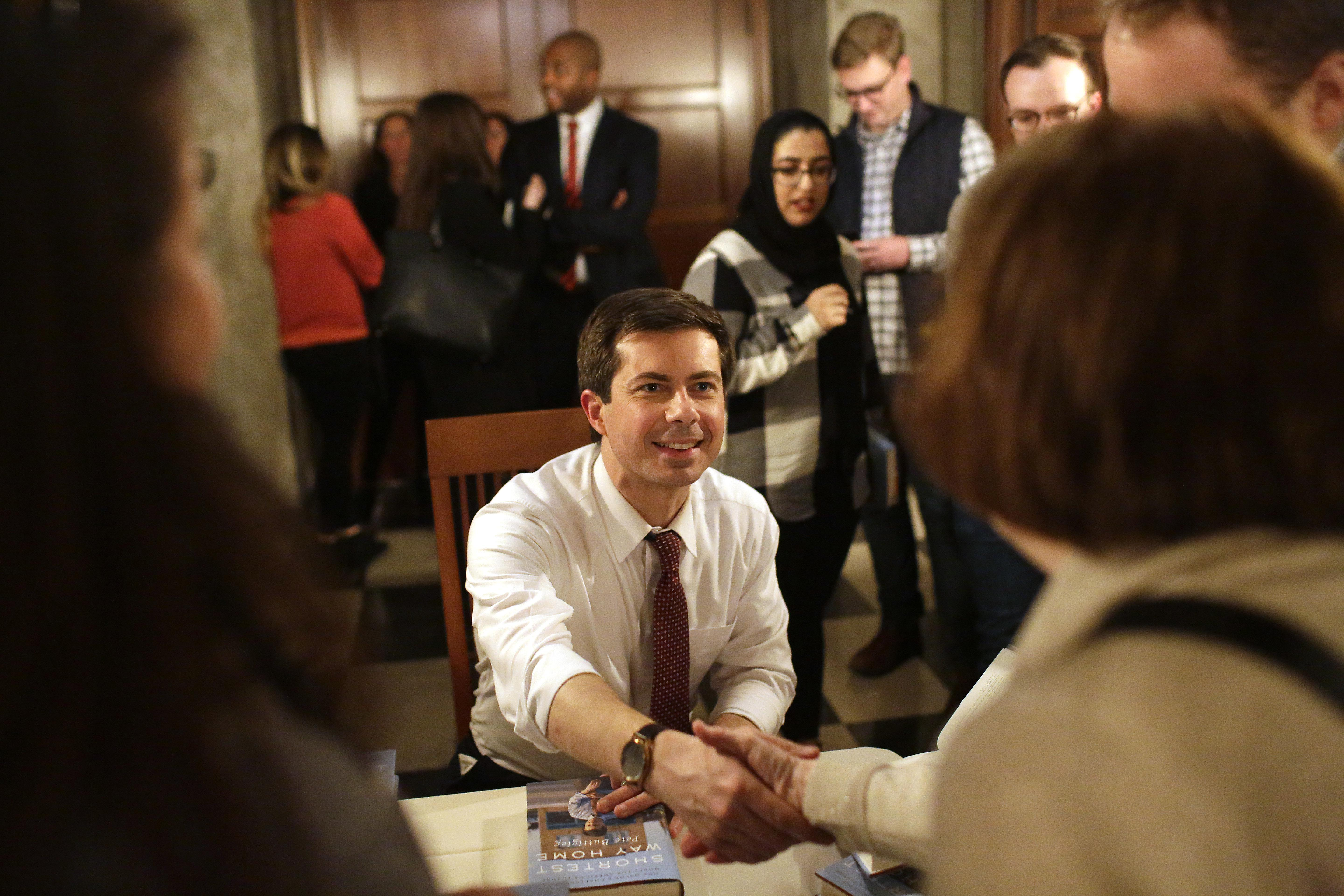 Pete Buttigieg greets a guest as he signs copies of his book in Chicago.