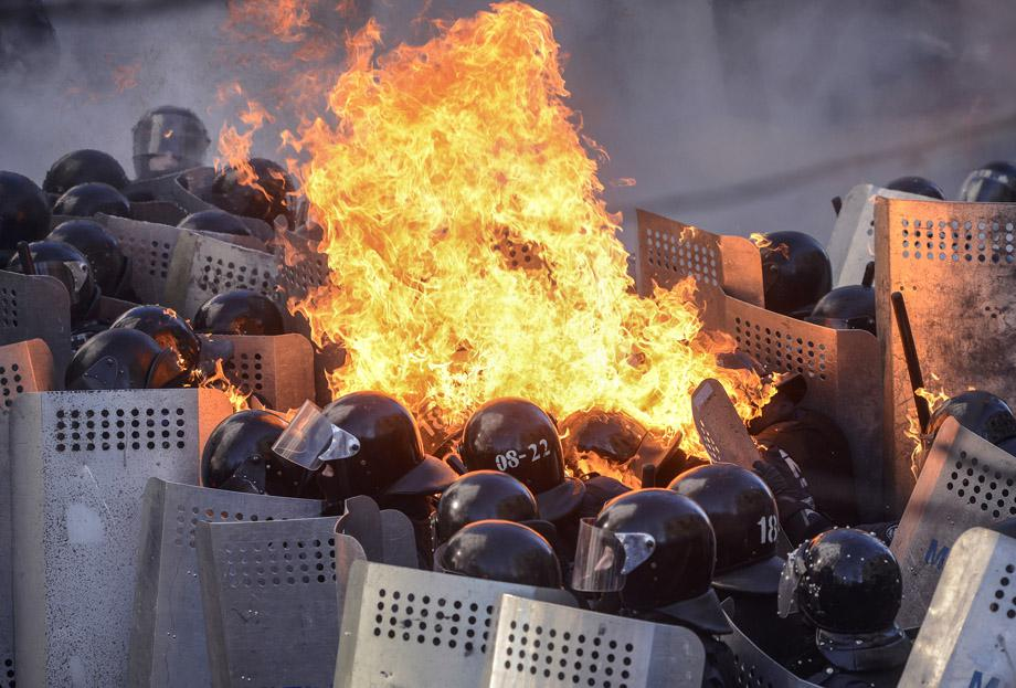 Government police catch fire from Molotov cocktails hurled by protesters as they stand guard during clashes in Kiev on Feb. 18, 2014.