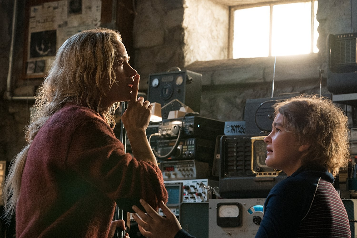 Emily Blunt (left) looks at something, petrified. She makes the shushing motion. Her daughter, played by Millicent Simmonds (right) has a scared expression and reaches for her with one arm.
