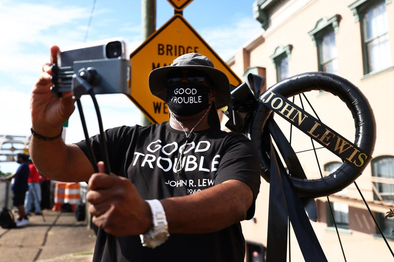 Alan Hill takes a selfie next to a memorial as he awaits the funeral procession of civil rights icon, former US Rep. John Lewis (D-GA) on July 26, 2020 in Selma, Alabama.