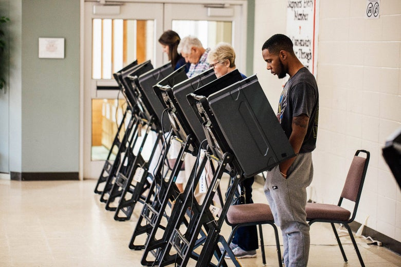 A row of voters voting at booths.