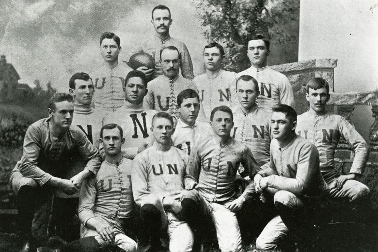 Black-and-white photo of an old-fashioned football team posing for the camera.