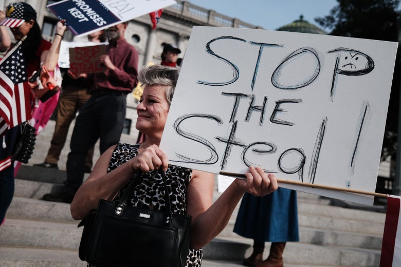 "A protester holds a ""Stop the Steal"" sign at the Pennsylvania state capital."