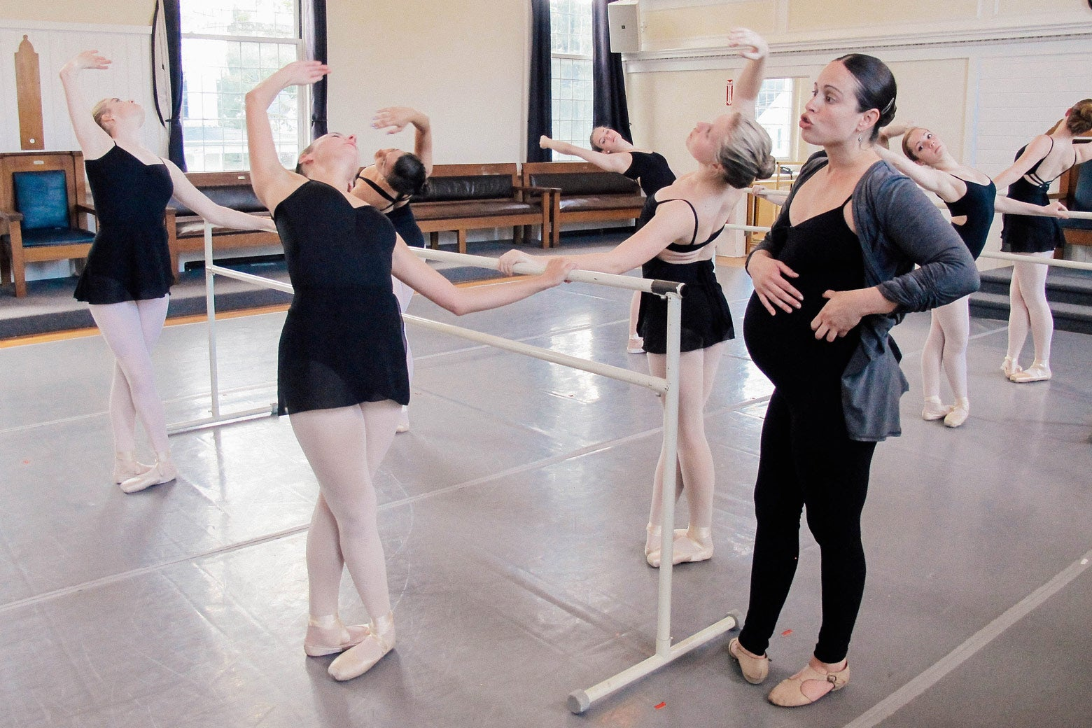 Anecia teaches students on the bar in a ballet class.