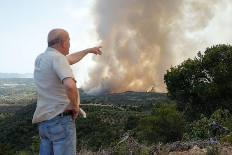 A resident points to a forest fire raging near Maials in the northeastern region of Catalonia on June 27, 2019. - A Spanish forest fire raged out of control amid a European heatwave, devouring land as hundreds of firefighters battled through the night, local authorities said. (Photo by Pau Barrena / AFP)        (Photo credit should read PAU BARRENA/AFP/Getty Images)