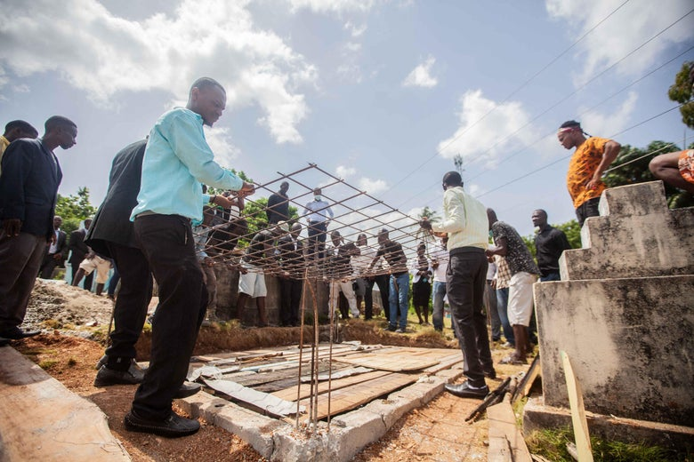 Haitians work on rebuilding a school.