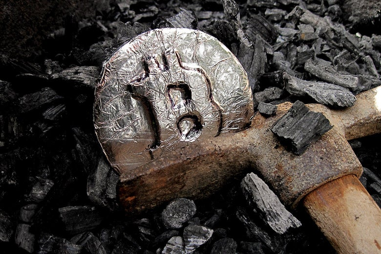 A miner's ax next to a medallion with the Bitcoin logo on it.