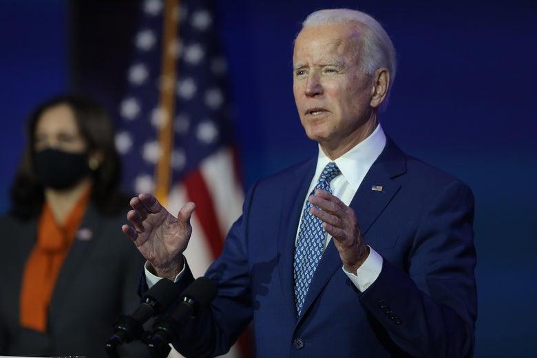 Joe Biden gestures while speaking in front of U.S. flags and Kamala Harris.
