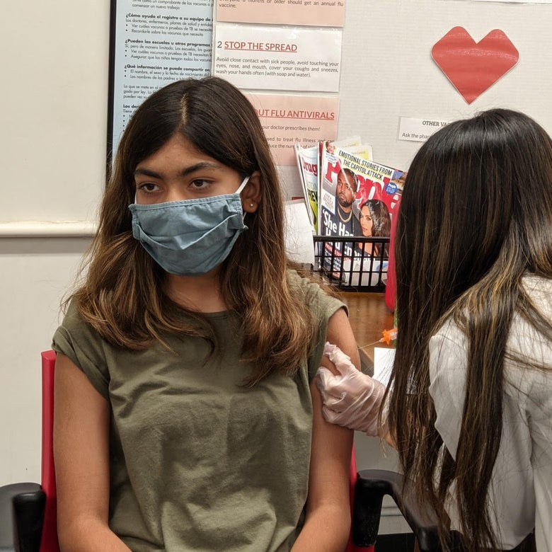 A girl wearing a mask received a vaccine.