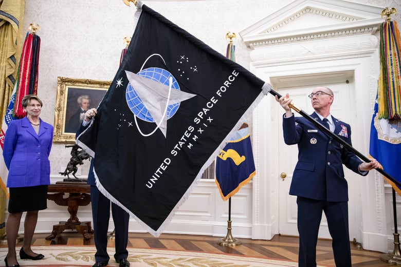A man in uniform holds a Space Force flag in the Oval Office.