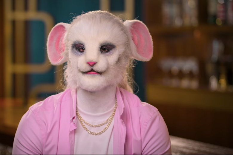 Man in pink shirt wearing realistic mouse mask.