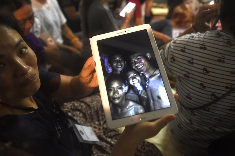 A family member shows the latest pictures of the missing boys taken by rescue divers inside Tham Luang cave.